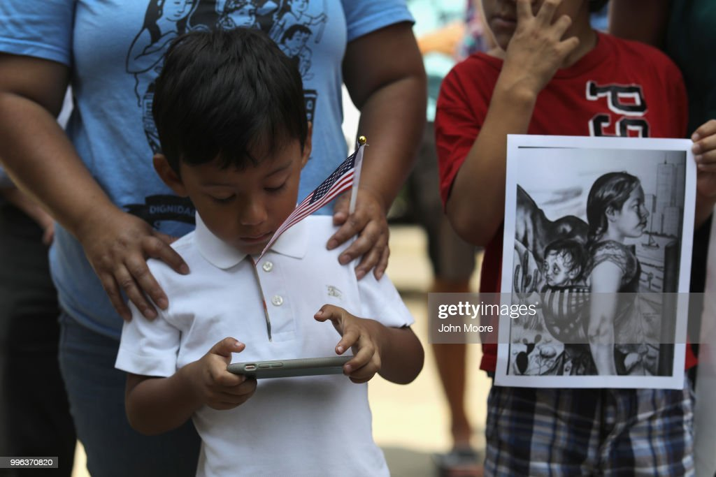 A boy plays on his mobile phone as protesters rally against the separation of immigrant families in front of a U.S. federal court on July 11, 2018 in Bridgeport, Connecticut. The rally was in support of two Central American children separated from their parents as a result of the Trump administration's 'zero tolerance' policy on undocumented immigration at the southern border. The two children, who are reportedly being held in a facility in Groton, CT were to appear at a court hearing ahead of possible reunification with their parents.