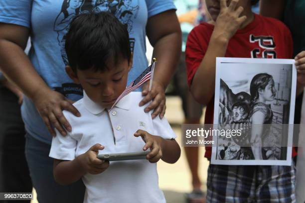 A boy plays on his mobile phone as protesters rally against the separation of immigrant families in front of a US federal court on July 11 2018 in...
