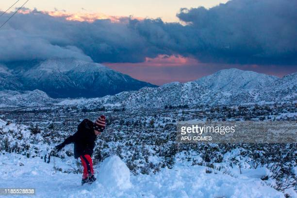 A boy plays on the snow at San Bernardino Forest on November 29 2019 in Wrightwood California A new storm is forecast to sweep in from the west in...
