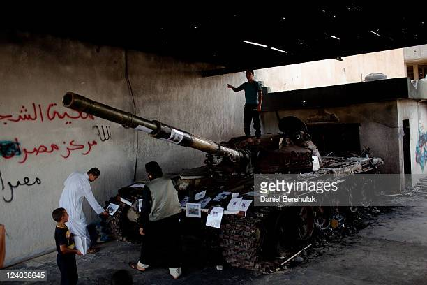Boy plays on top of a tank destroyed by fighting, as workers from an NGO attach photographs of people who were killed or severely affected by the...