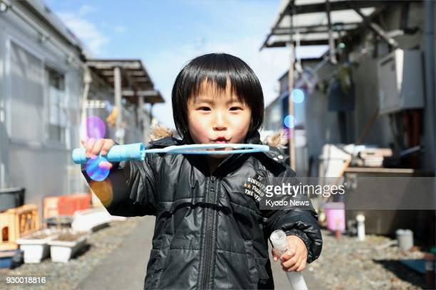 Boy plays outside temporary housing in Otsuchi, Iwate Prefecture on March 10 a day before the seventh anniversary of the March 11 earthquake-tsunami...