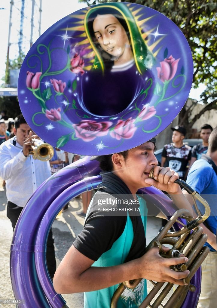 A boy plays the tuba at Kilometro 30 community, near the Acapulco resort in Guerrero State, Mexico, on February 14, 2018. Violence in the state of Guerrero claimed the lives of two priests on February 5, 2018. / AFP PHOTO / Alfredo ESTRELLA / TO