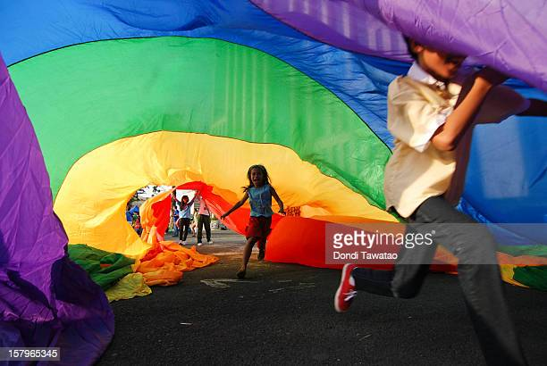 A boy plays under a rainbow flag during the Manila Gay Pride March on December 8 2012 in Makati Philippines Although frowned upon by the mainstream...