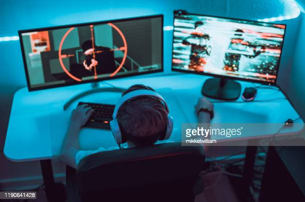 boy plays video game online and sits in front of two big computer monitors - esport stock pictures, royalty-free photos & images