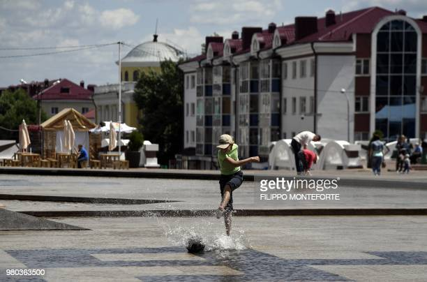 A boy plays with a ball in a fountain in the city of Saransk on June 21 during the Russia 2018 World Cup football tournament