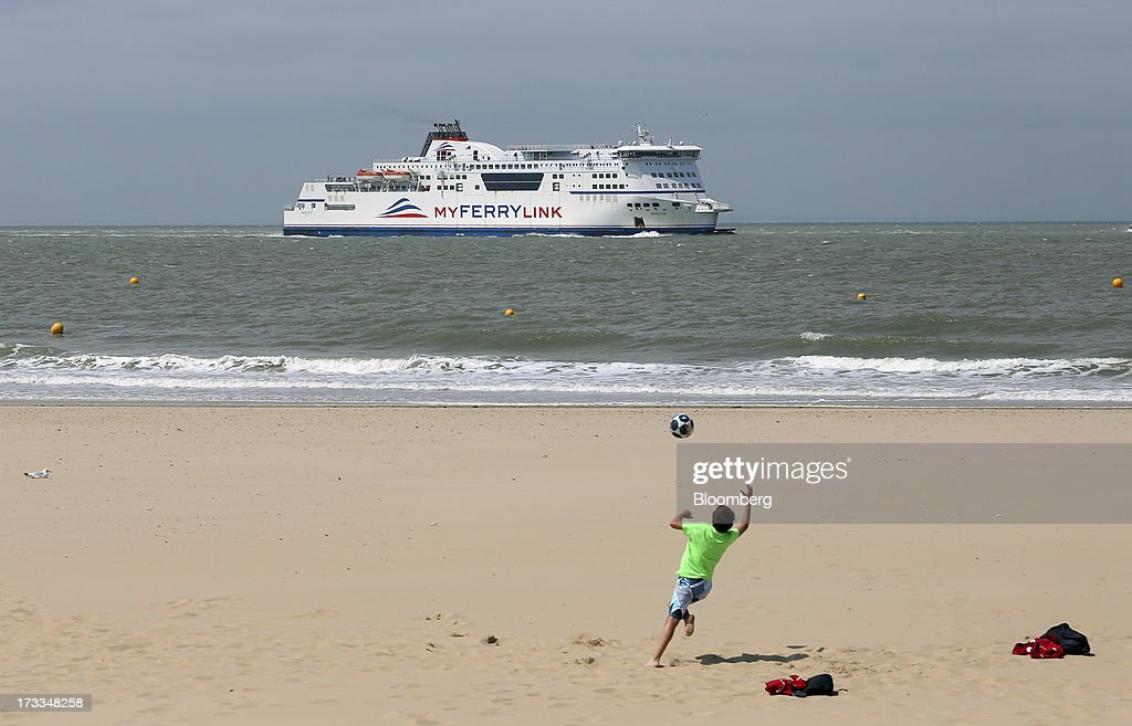 A boy plays with a ball on the beach as the passenger ferry 'Berloiz', operated by MyFerryLink, a unit of Groupe Eurotunnel SA, sails towards the Port of Calais in Calais, France, on Thursday, July 11, 2013. Eurotunnel was barred by the U.K. Competition Commission from operating a ferry service between France and Dover in the U.K. on concern it would give it too much dominance on the Channel traffic route. Photographer: Chris Ratcliffe/Bloomberg via Getty Images