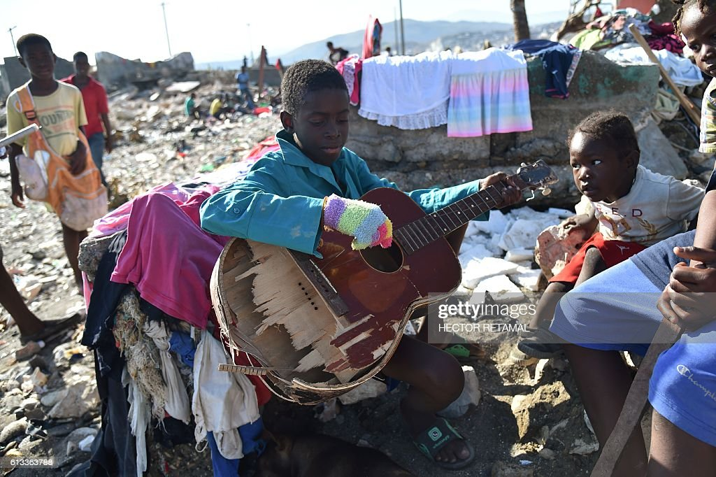 A boy plays with a broken guitar while sitting in rubble left by the Hurricane Matthew, in Jeremie, Haiti, on October 8, 2016. The full scale of the devastation in hurricane-hit rural Haiti became clear Saturday as the death toll surged past 400, three days after Matthew leveled huge swaths of the country's south. / AFP / HECTOR