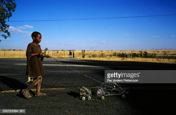 A boy plays with a homemade car made of wire along a road on July 28 2000 in Eastcourt Natal Province South Africa His father built the car and its...