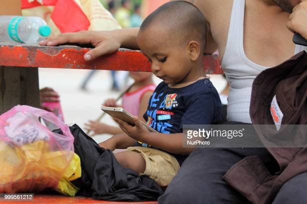 A boy plays with a Mobile Phone outside Pragati Maidan Metro Station In New Delhi on July 15 2018