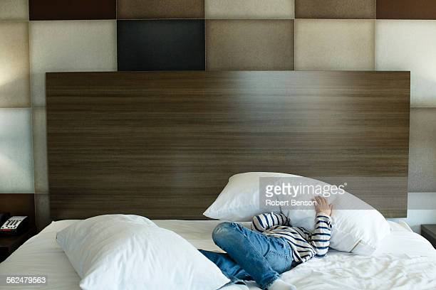 A boy plays with a pillow on a motel room bed.