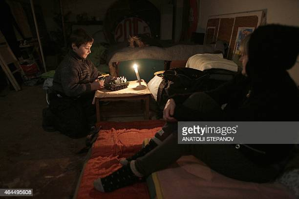 A boy plays with a toy tank as he sits along with his family in a bomb shelter after their house was destroyed in the village of Myronivske near...