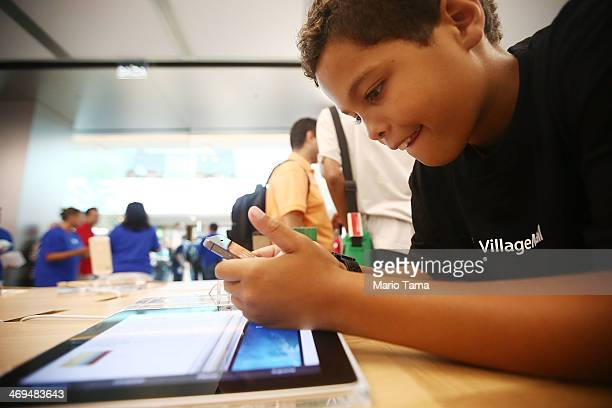 A boy plays with an iPhone in Brazil's first Apple retail store minutes after it opened to the public for the first time in the Village Mall shopping...