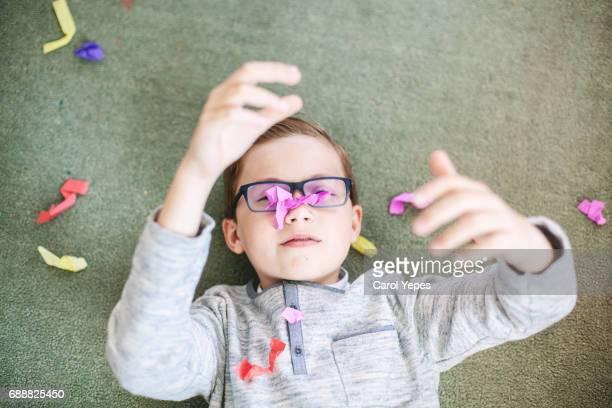 boy plays  with confetti lying on floor