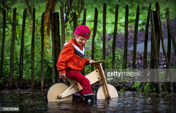 A boy plays with his bike in a pool in a camping site during heavy rainfall on Castricum at the Dutch Northsea coast on August 4 2010 AFP PHOTO / ANP...