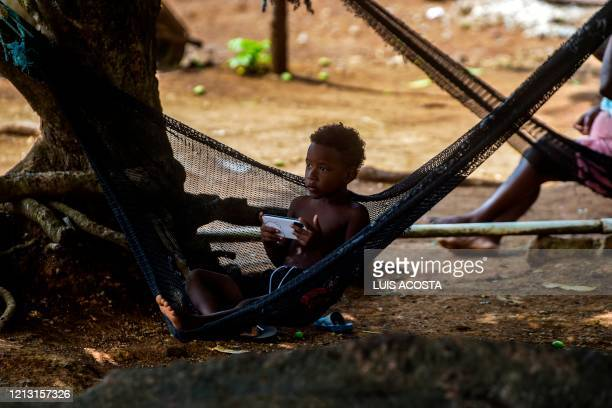 A boy plays with on a cell phone at Pedro Gonzalez Island Pearl archipelago Panama during a food delivery for lowincome families on May 15 2020 The...