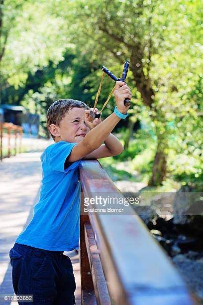 Boy plays with slingshot