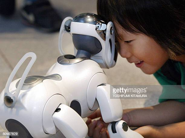 A boy plays with Sony's latest entertainment robot dog AIBO ERS7 during AIBO's 5th anniversary exhibition in Tokyo 29 May 2004 More than 130000 units...