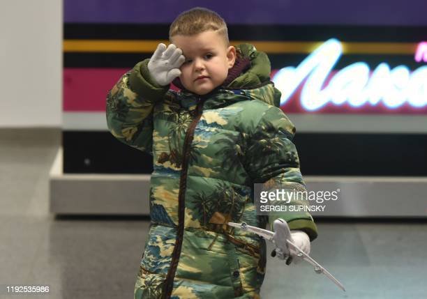 A boy plays with toy plane as he and his mother attend at the arrival gate of the Boryspil airport outside Kiev on January 8 2020 A Ukrainian...