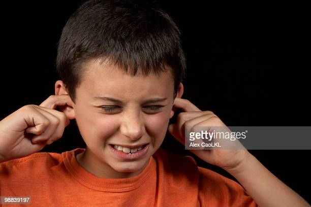 boy plugging ears to loud noise - fingers in ears stock pictures, royalty-free photos & images