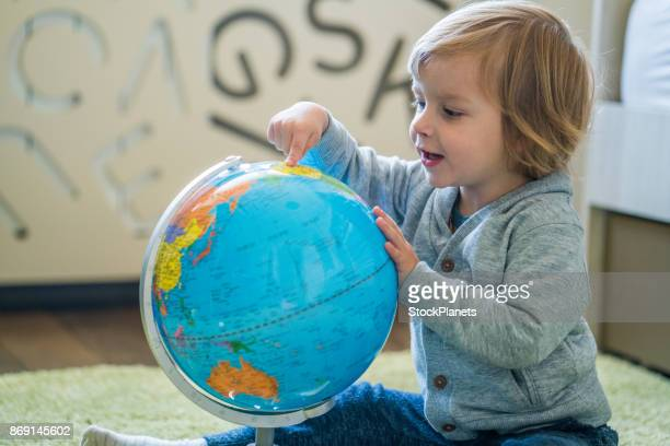 boy pointing a spot on the globe - baby pointing stock photos and pictures