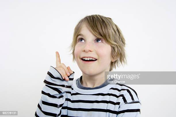 Boy (10-11) pointing and looking upwards, portrait