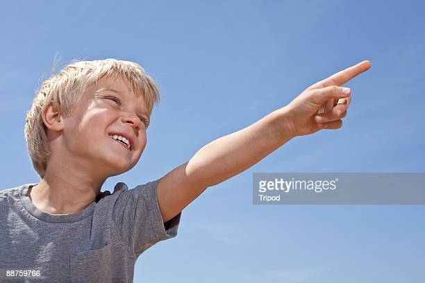 Boy (5-7) pointing and smiling, low angle view