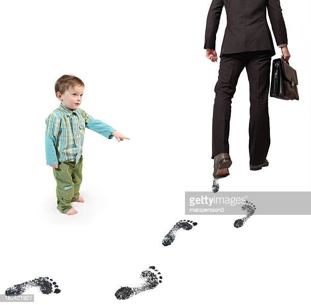Boy pointing at business man leaving carbon footprints
