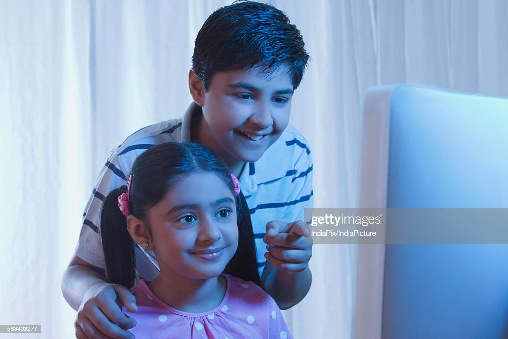 Boy pointing something out to girl on computer : Stock Photo