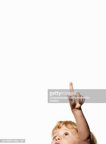Boy (2-3) pointing up on white background (cropped)