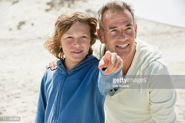 Boy pointing with his grandfather on the beach