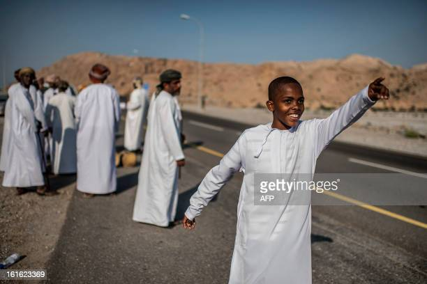 A boy points as Omanis wait for cyclists during the third stage of the Tour of Oman from Nakhal Fort to Wadi Dayqah Dam on February 13 in Oman The...