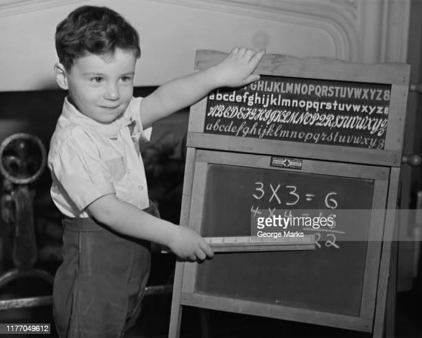 boy points at blackboard with ruler - schulkind nur jungen stock-fotos und bilder