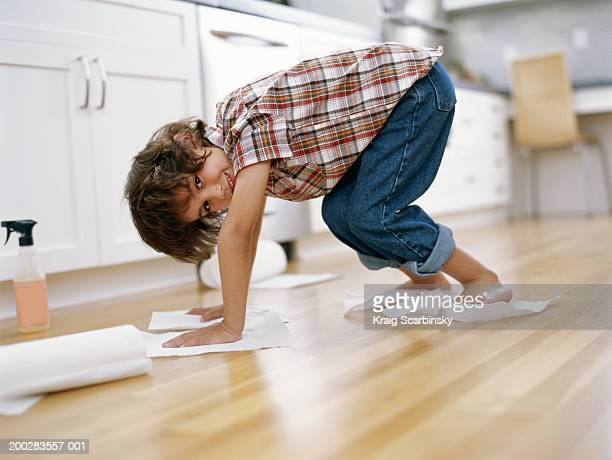 Boy (5-7) polishing floor with paper towel under hands and feet