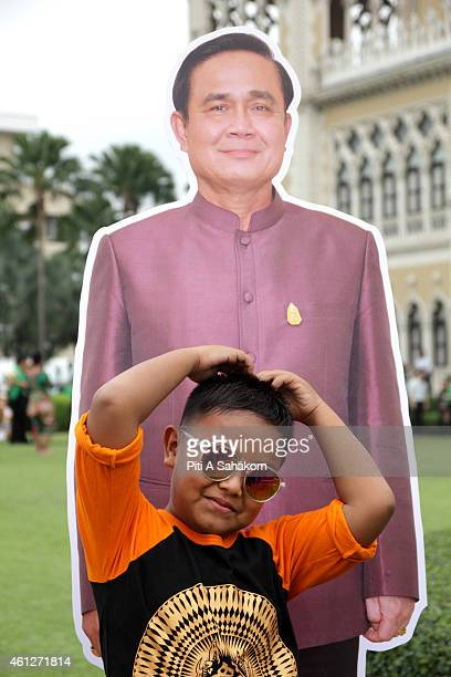 A boy pose for photograph with a Prime Minister Prayut Chanocha cardboard cutout during National Children's Day at The Government House in Bangkok...
