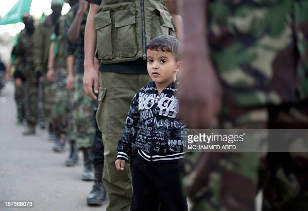Boy poses as he stands among young members of the Palestinian Islamist movement Hamas during an anti-Israel march on the first anniversary of...