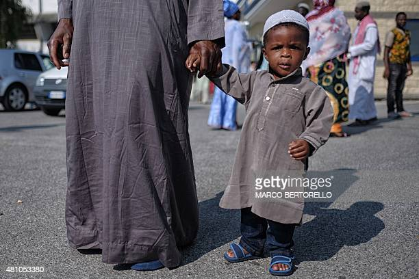 A boy poses during a celebration of Eid alFitr marking the end of the fasting month of Ramadan in a gymnasium in Saluzzo near Turin on July 17 2015...