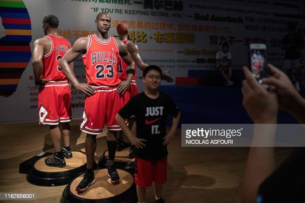 Boy poses for a photo in front of a life-size wax figure of US basketball player Michael Jordan at the NBA exhibition in Beijing on August 19, 2019....