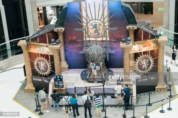 A boy poses for photos with a lifesize replica of the Iron Throne in the popular TV drama Game of Thrones in a department store on August 09 2017 in...