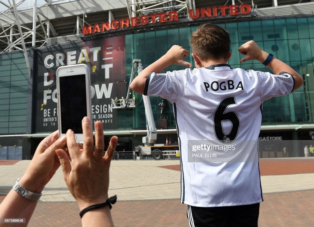 TOPSHOT - A boy poses for pictures after purchasing a Manchester United shirt with the name and squad number of recent signing French midfielder Paul Pogba outside Old Traford in Manchester, north west England, on August 9, 2016. The world record for a transfer fee was shredded Tuesday when French superstar Paul Pogba completed a sensational return to Manchester United from Juventus for 105 million euros ($116 million). / AFP / PAUL