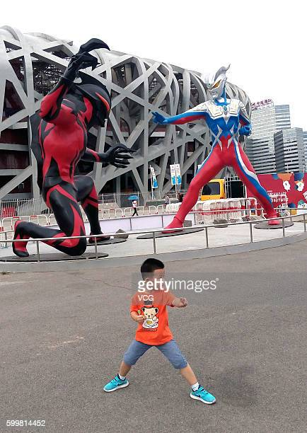 """Boy poses in front of sculptures of a 5-meter-tall superhero """"Ultraman"""" and a monster Belial beside the National Stadium on September 6, 2016 in..."""