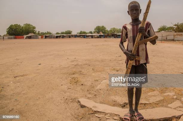 A boy poses with a wooden gun on March 7 2017 in Leer where famine has been declared since February 2017 International NGOs have left the area after...