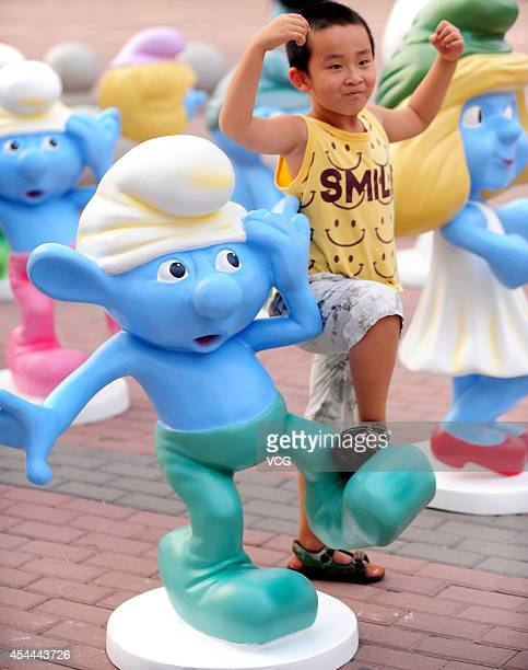 A boy poses with replicas of Smurfs on August 31 2014 in Shenyang Liaoning province of China More than 50 replicas of Doraemon coupled with 50...