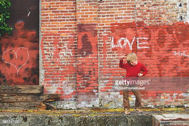 Boy posing in front of wall with graffiti