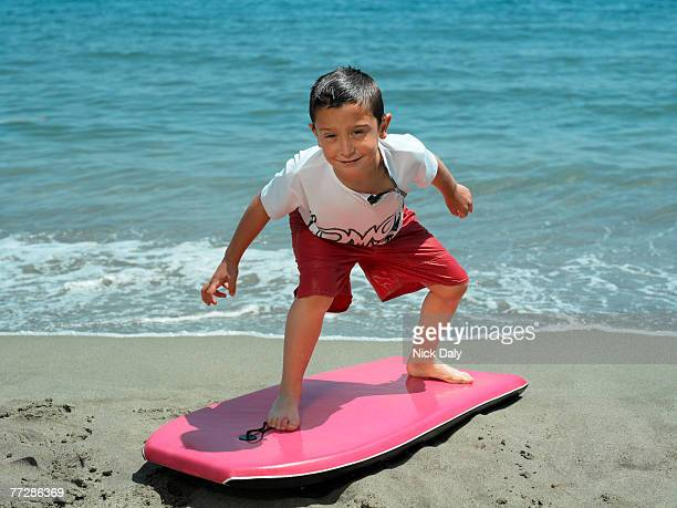 Boy posing on boogie board by the surf