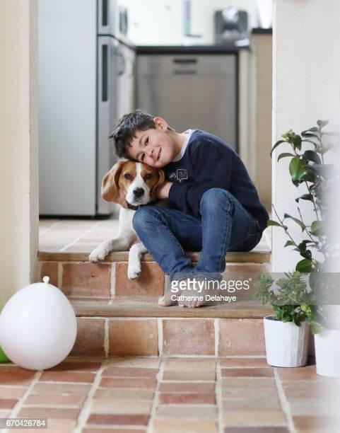 A boy posing with his dog, a beagle