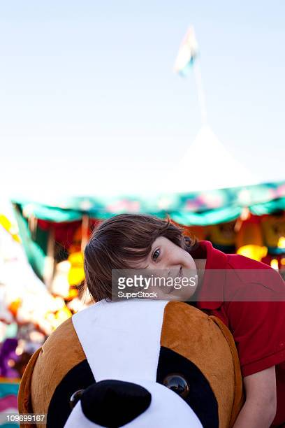 Boy posing with toy dog winning at fair, front view