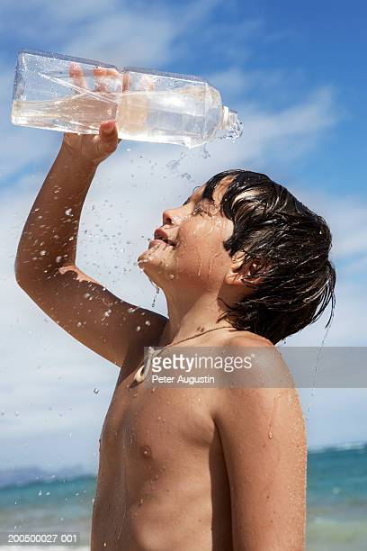 Boy (12-13) pouring bottled water over himself on beach