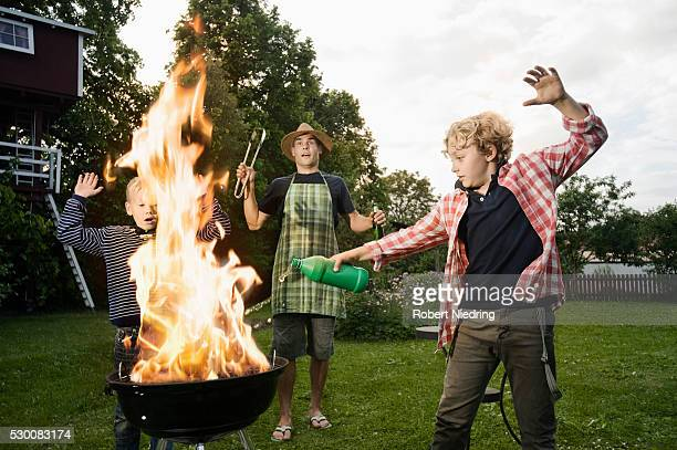 Boy pouring methylated spirit on barbecue fire