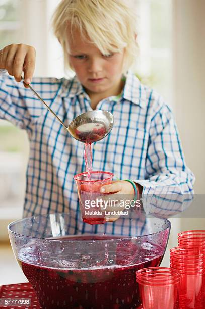 A boy pouring out a fruit drink into a glass Sweden.