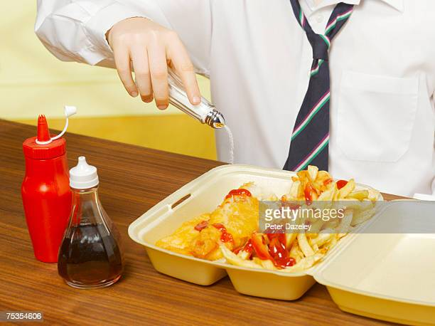 Boy (8-10) pouring salt on fish and chips